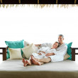 Couple lying together in resort bedroom - Stock Photo