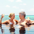 Romantic mature couple in pool with champagne by the sea - Stock Photo