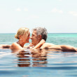 Loving mature couple enjoying their vacation in a swimming pool by the seaside - Stock Photo