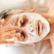 Mature man receivng spa facial treatment - Stock Photo