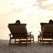 Royalty-Free Stock Photo: Couple sitting on chairs at the beach enjoying sunset