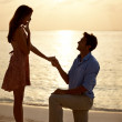 Man proposing marriage to surprised woman at beach sunset - Foto Stock