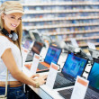 Happy young lady in consumer electronics store - Stock Photo