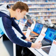 Young man in consumer electronic store looks at laptop - Stock Photo