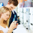 Young couple checking out new digital camera at store - Stock Photo
