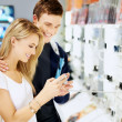 Happy couple at consumer electronics shop buying digital camera - Stock Photo