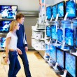 Young couple in electronics store looking at TVs - Foto de Stock