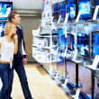 Young checking out new television sets in megastore - Stockfoto