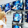 Young couple in megastore looking at TVs - Stock Photo