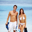 Young couple with snorkelling gear at the beach - Foto Stock