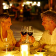 Mature couple enjoying candlelight dinner in a restaurant - Stock Photo