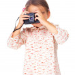 Pretty small girl shooting with camera over white - Stock Photo