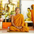 Seated monk in Buddhist temple - Stock Photo