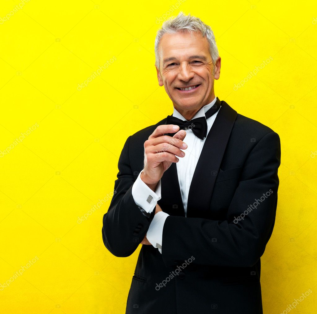 Portrait of smart senior guy wearing tuxedo isolated over yellow background — Stock Photo #12151244