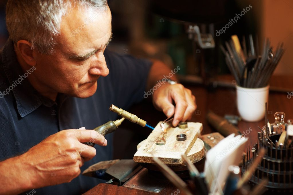 Jeweler using a blowtorch while he works on a ring — Stock Photo #12151442