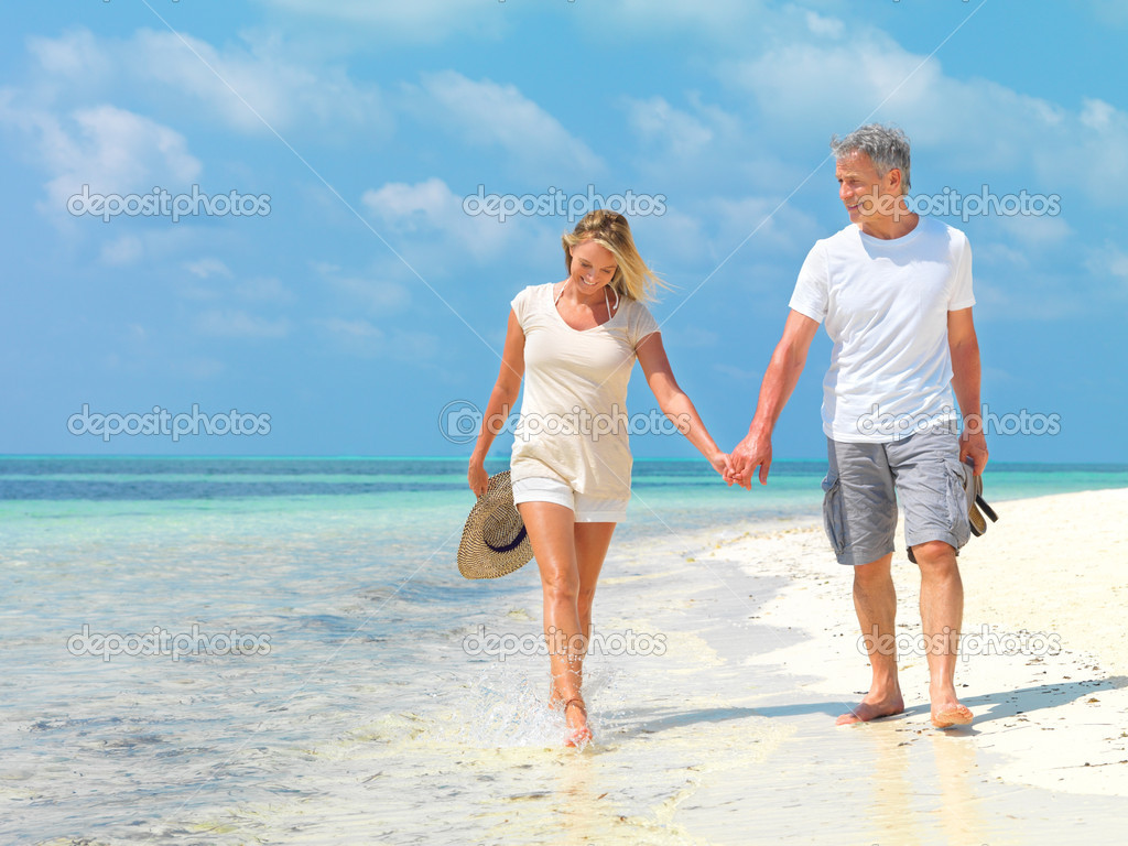 Portrait of happy mature couple walking on the beach holding hands — Stock Photo #12151989