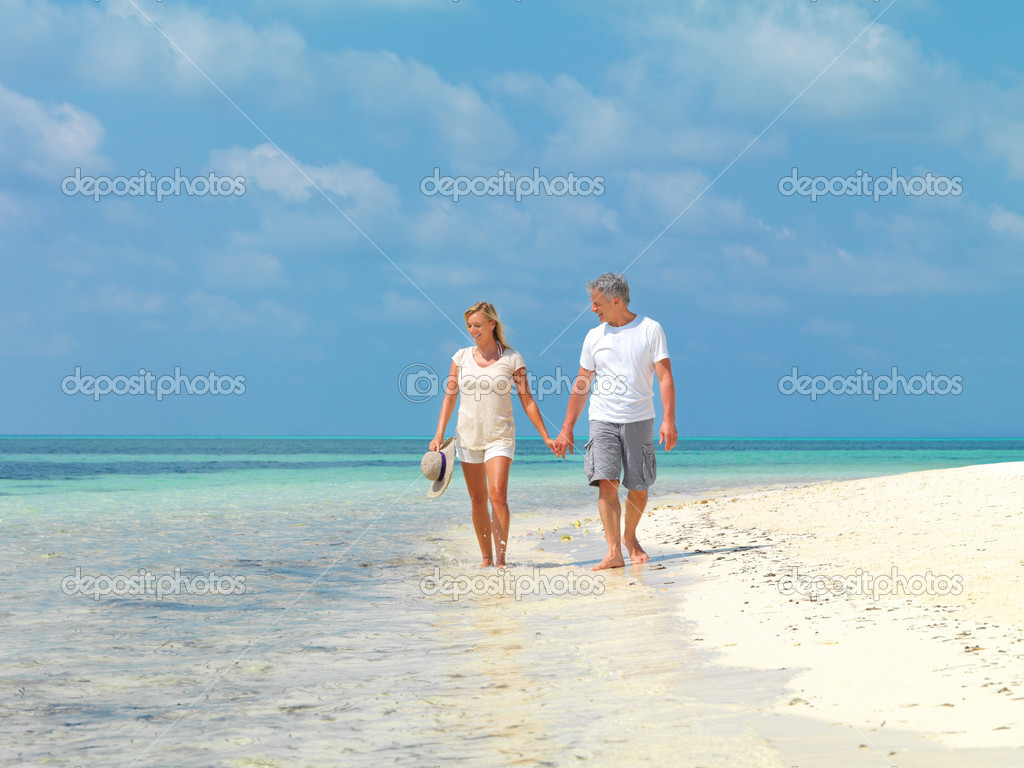Portrait of relaxed mature couple walking by the sea shore holding hands  Stock Photo #12151990