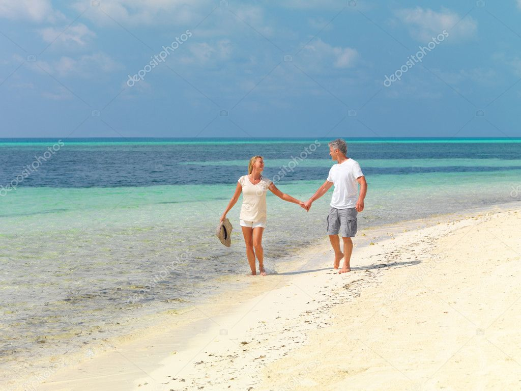 Portrait of happy mature couple strolling on the beach with hand in hand — Stock Photo #12151996