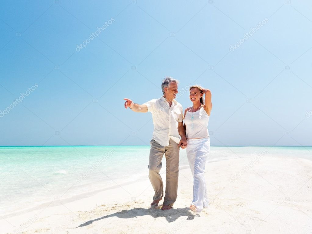 Portrait of romantic mature couple having a walking on the sea shore — Stock Photo #12152359