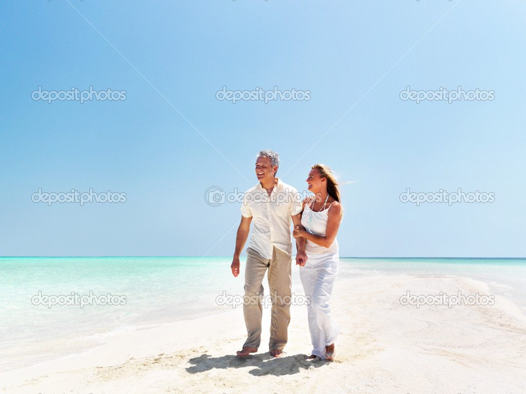 Portrait of happy middle aged couple walking together on the beach — Stock Photo #12152362