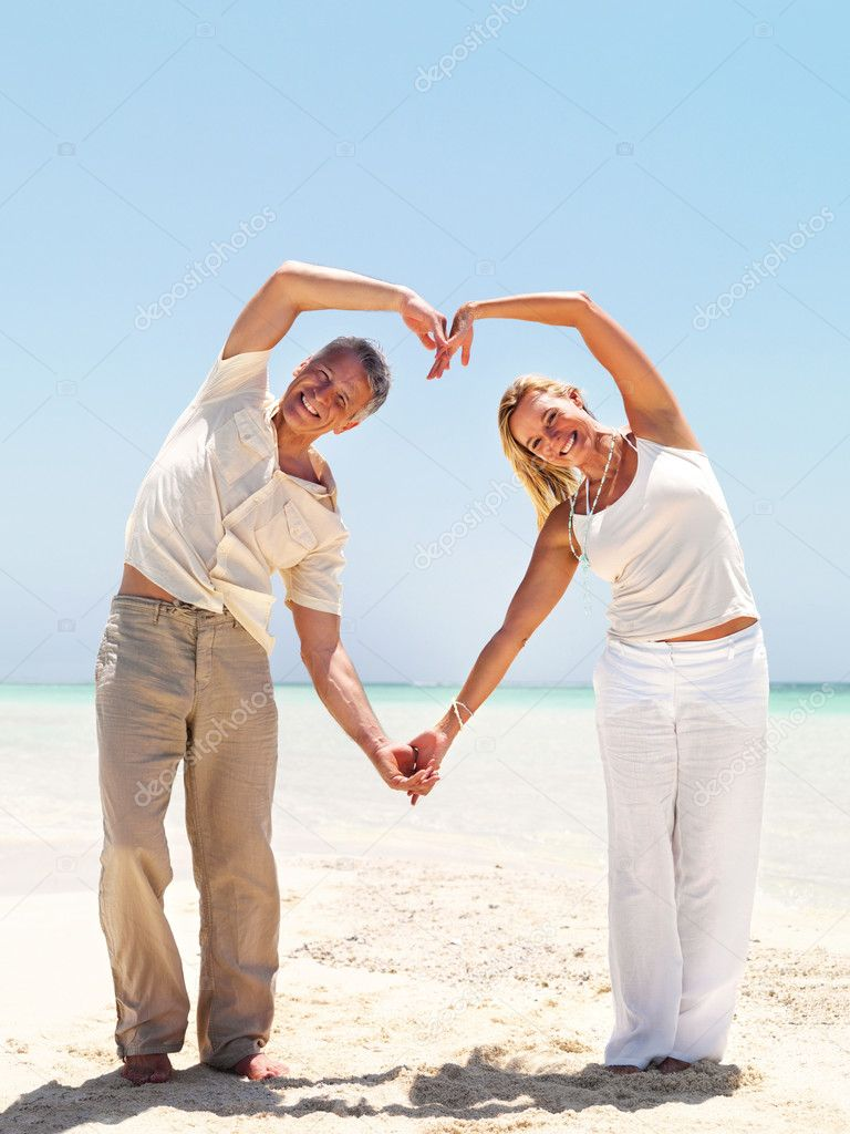 Portrait of middle aged at the beach making a heart shape with their hands  Stock Photo #12152409