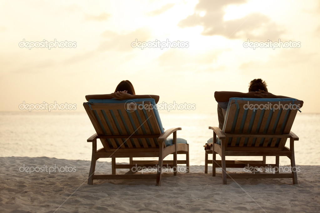 Couple sitting in the chairs watching sunset at the beach — Stock Photo #12152669
