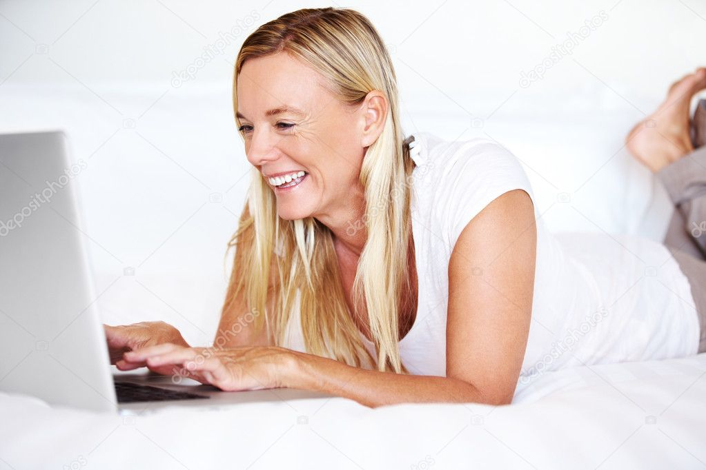 Happy mature woman lying on bed using laptop smiling — Stock Photo #12153460