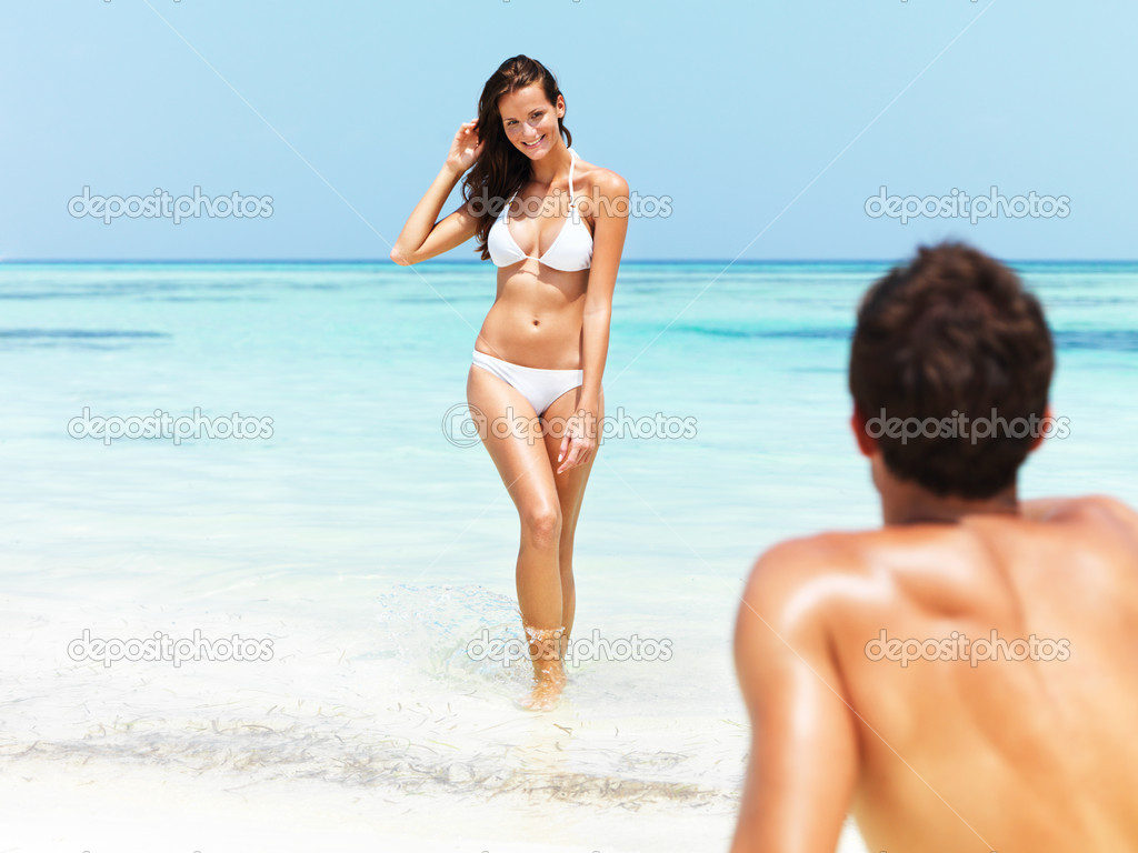 Gorgeous tanned female emerges from the blue ocean as her muscular boyfriend looks on — Stock Photo #12153918