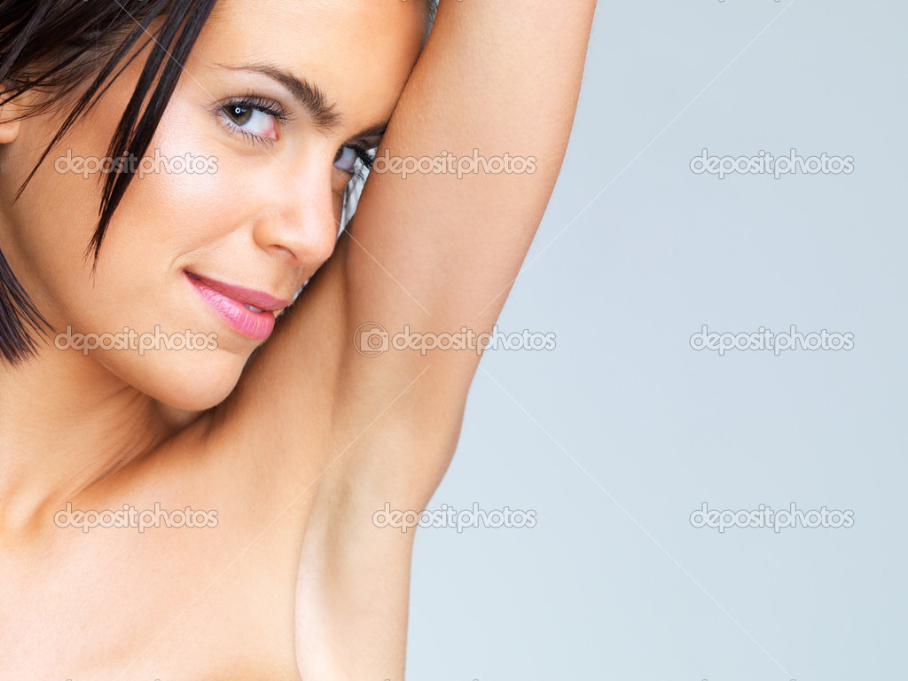 Copyspace- beautiful brunette woman showing armpit and looking at camera — Stock Photo #12154010