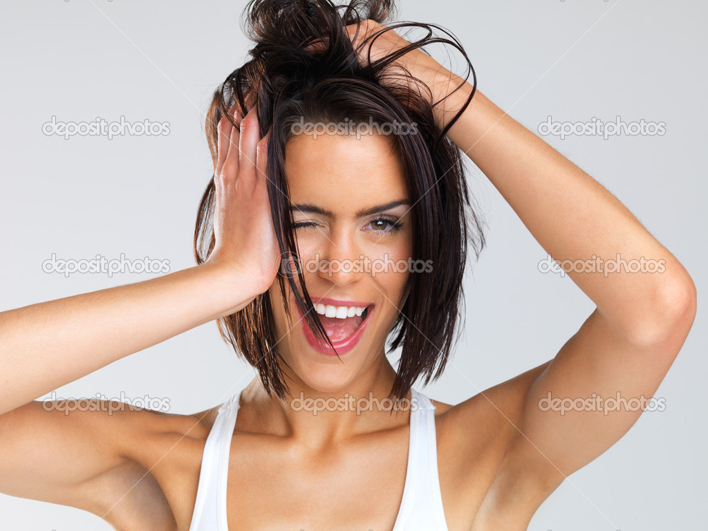 Portrait of beautiful young brunette messing up her hair with her hands — Stock Photo #12154055