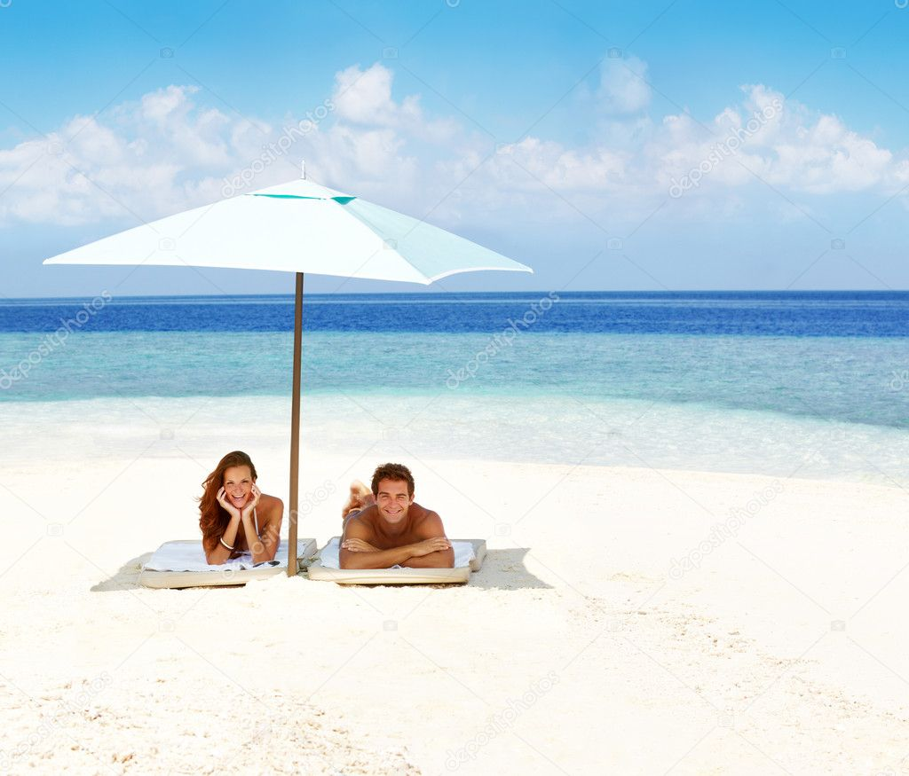 Portrait of a beautiful tanned couple lying on the beach underneath an umbrella - Copyspace — Stock Photo #12154338