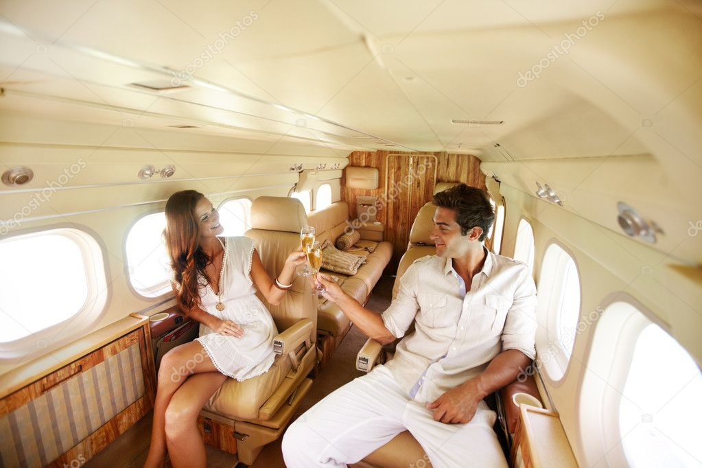 Blissful couple toast the beginning of their holiday with champagne in a planes cabin — Stock fotografie #12154408