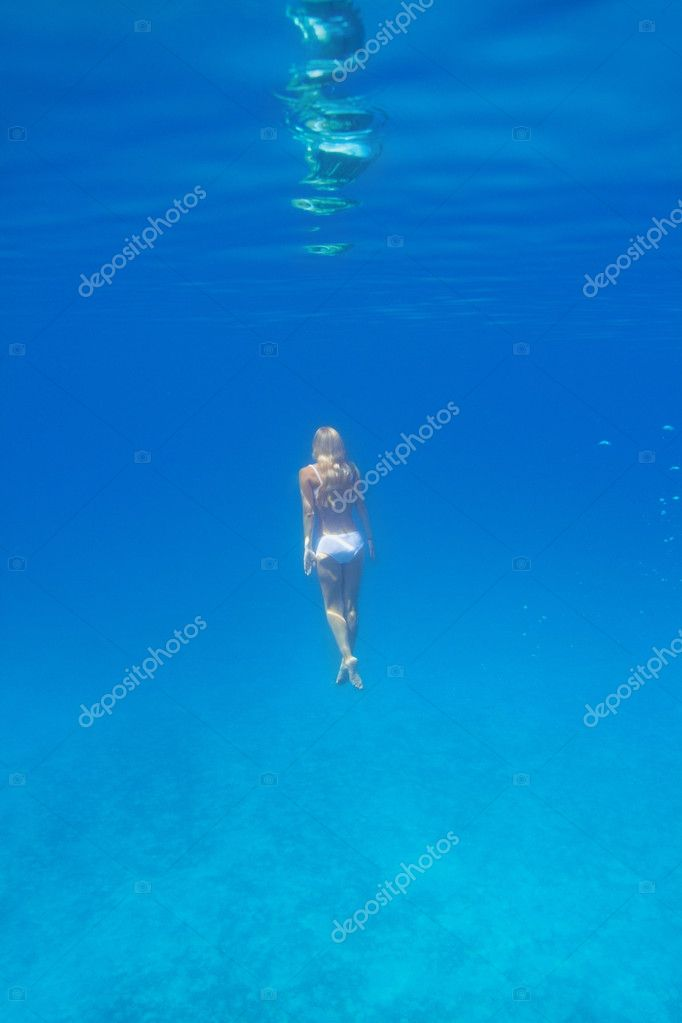 Young woman underwater gently rising to the surface facing away from the camera - copyspace — Stock Photo #12154506