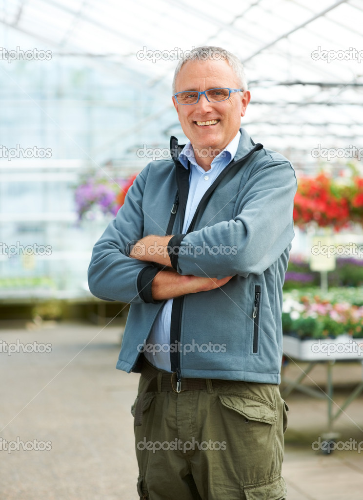 Portrait of mature caucasian male florist standing with arms crossed smiling at camera — Stock Photo #12154596