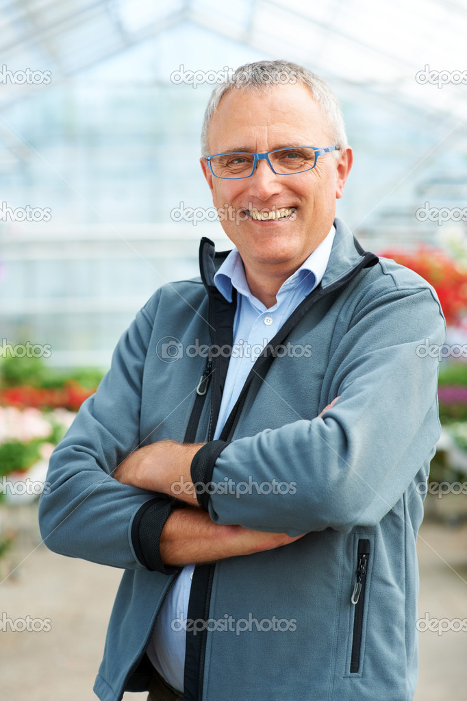 Portrait of mature caucasian male florist standing with arms crossed smiling at camera — Stock Photo #12154597