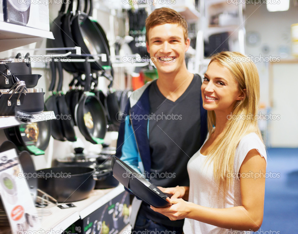 Young couple smiling at the camera while holding a frying pan in a homeware store  Stock Photo #12154665