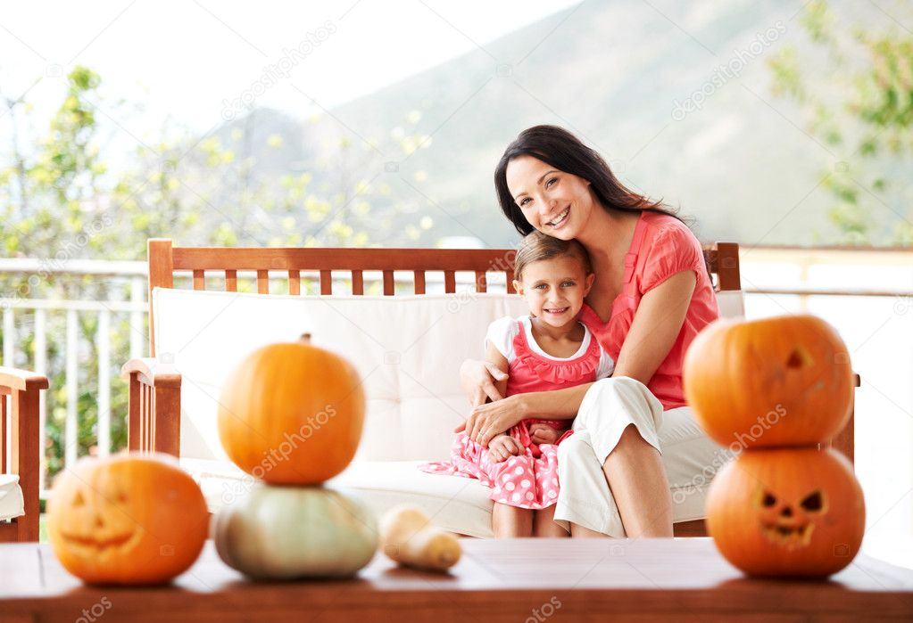Portrait of a mother and daughter hugging behind a table of pumpkins — Stock Photo #12236183