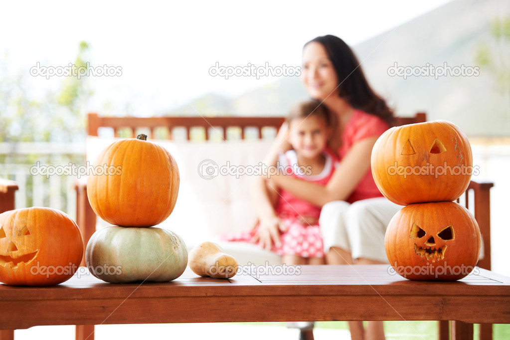 A table of carved pumpkins with a mother and daughter bonding in the background  Stock Photo #12236186
