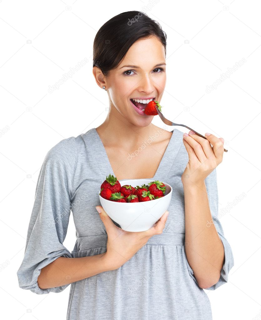 Lovely brunette eating a bowl of strawberries while smiling at the camera - portrait — Stock Photo #12236379