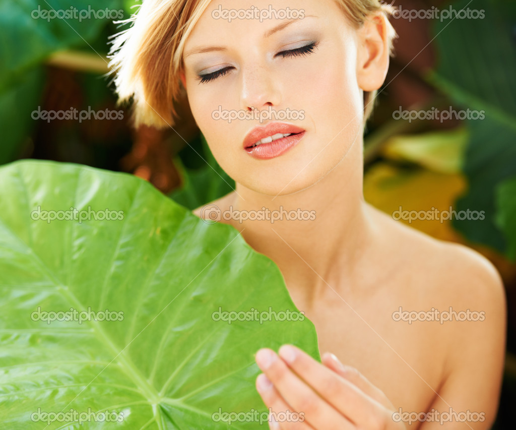 Natural beauty holding a leaf to her chest while outdoors  Stock Photo #12237046