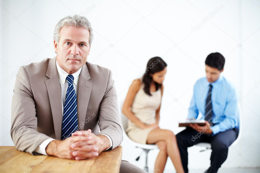 Mature businessman sitting at a desk and looking a the camera with two employees in the background — Stok fotoğraf #12237882