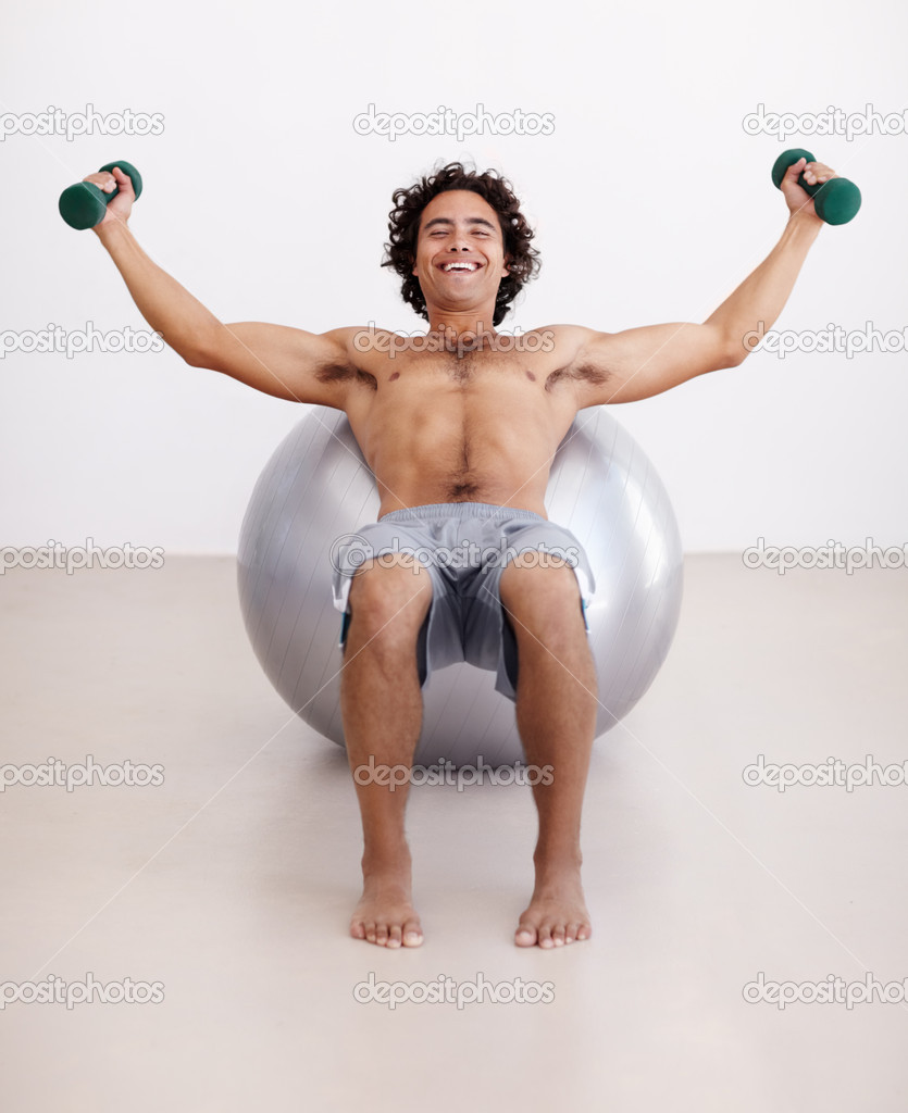 Portrait of a healthy young man lifting weights while balancing against a swissball  Stock Photo #12238377