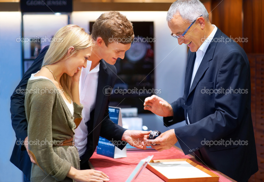 Mature jeweller showing a designer wristwatch to a happy young couple — Stock Photo #12238455