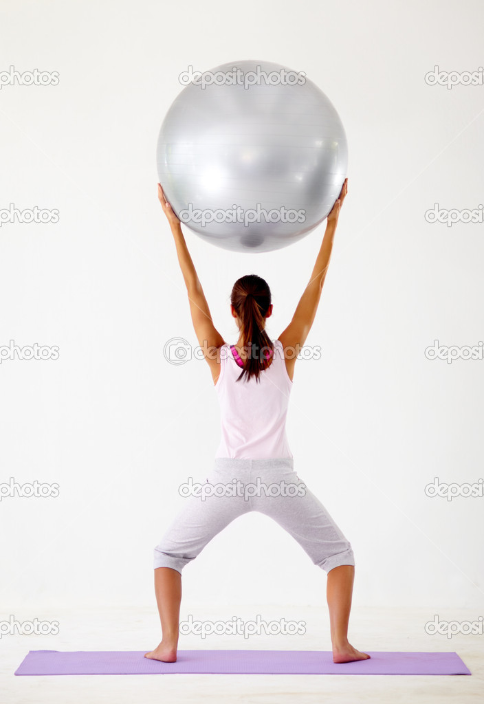 Rear view of a young woman squatting while holding a swiss ball above her head - Isolated on white — Stock Photo #12238909