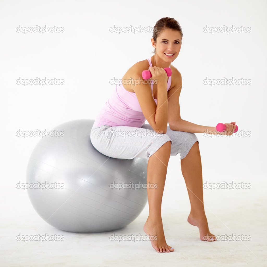Young woman sitting on a swiss ball and bicep curling dumbbells — Stock Photo #12238923