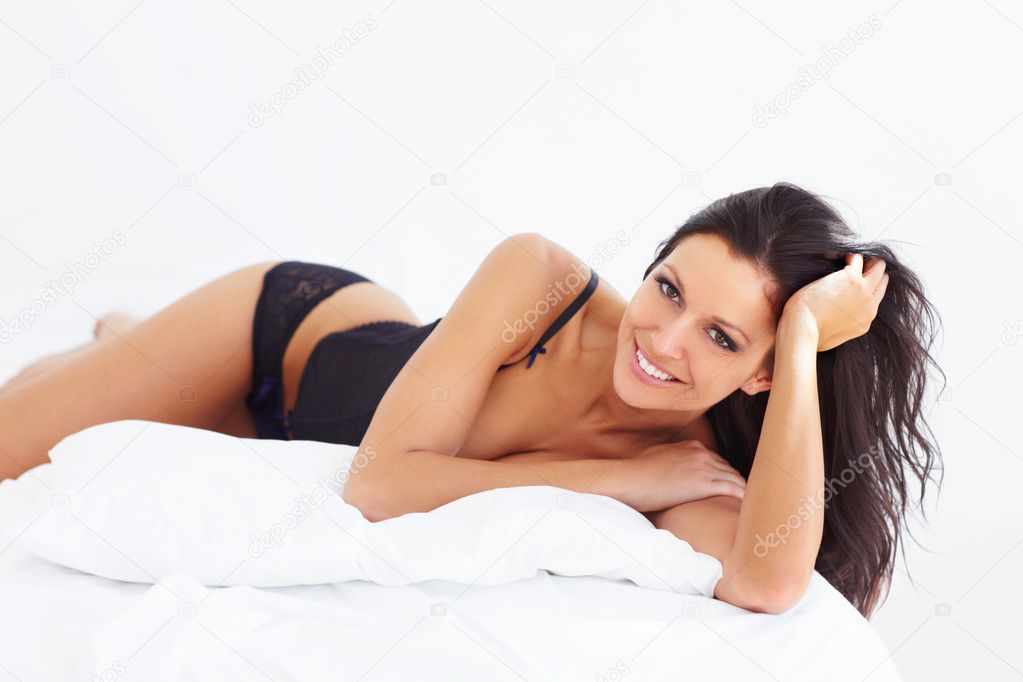 Sexy brunette stretched out on a bed wearing black lingerie - portrait — Stock Photo #12239820