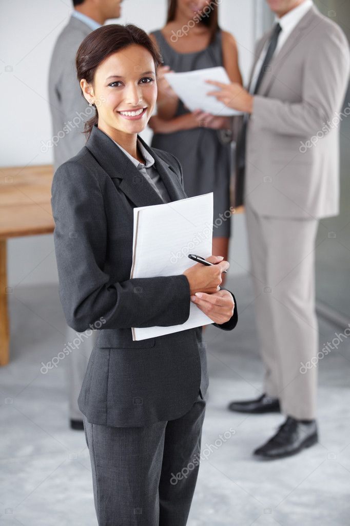 Portrait of a young executive holding a notebook and pen with her colleagues chatting in the background — Stock Photo #12239917