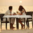 A young couple share a romantic dinner on the beach in the Maldi - Stock Photo