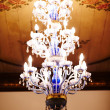 Ornate chandelier hanging from a decorated ceiling - Stock Photo