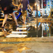 Tourist skipping over puddles in Thailand - 